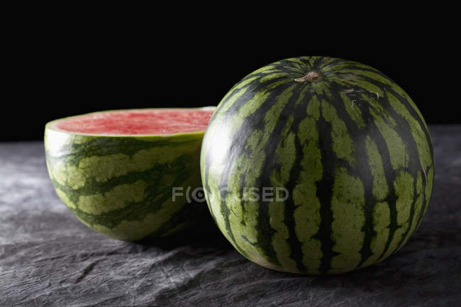 Fresh whole and halved watermelon on black fabric — Stock Photo