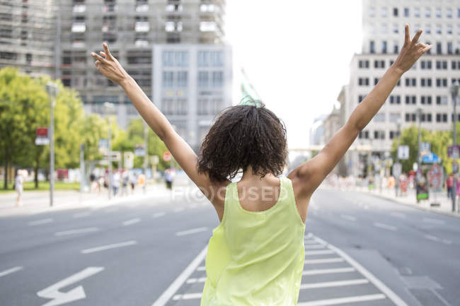 Young woman in the city, making victory sign, rear view — Stock Photo
