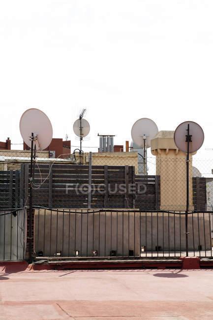 Platos de satélite de España, Barcelona, en el techo durante el día - foto de stock