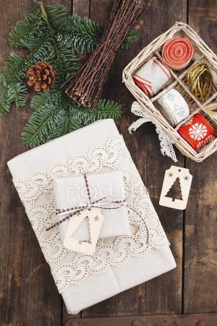 Weihnachtsgeschenk mit Geschenkanhänger und Verpackungsmaterial auf Holztisch — Stockfoto