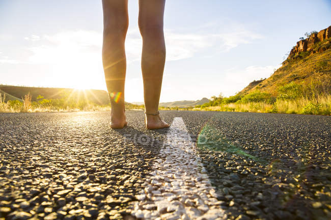 Young woman standing barefoot on empty road — Stock Photo