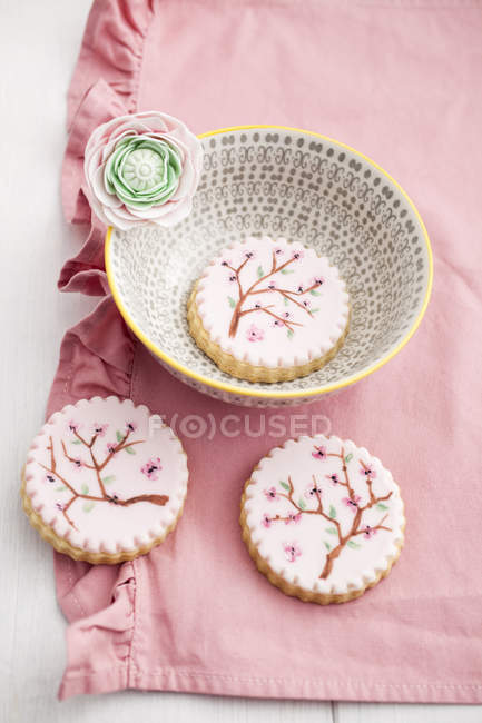 Painted pink sugar cookies with bowl on pink fabric — Stock Photo