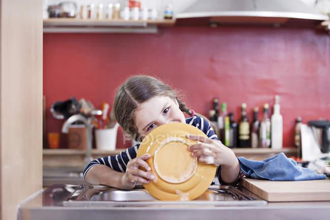 Портрет дівчинки миття пластин в кухонних раковині — стокове фото
