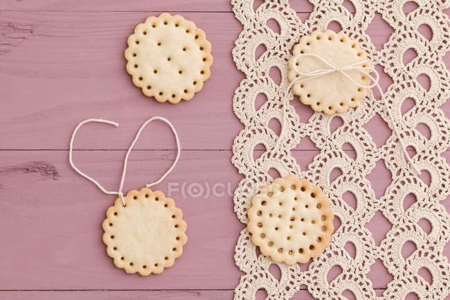 Galletas de mantequilla con diseño del peekaboo en mantel de ganchillo - foto de stock