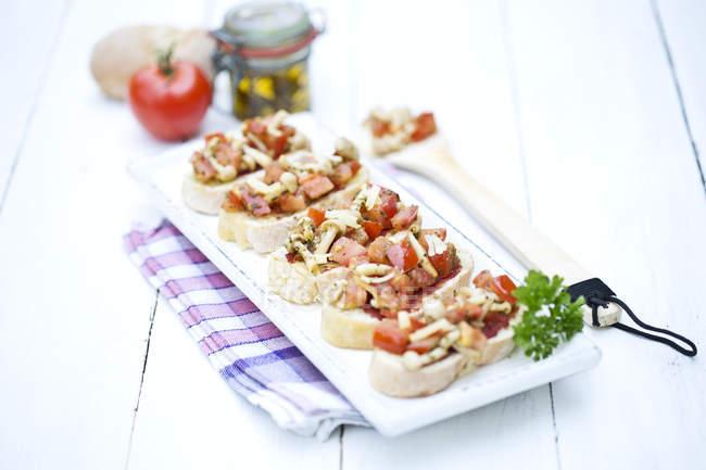 Teller mit Bruschetta mit Tomaten, weiße Shimeji Pilze, Kräuter und Olivenöl auf Holztisch, Nahaufnahme — Stockfoto