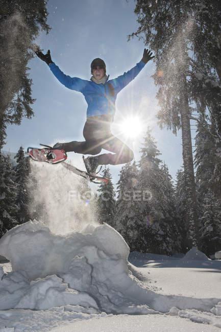 Homme avec raquettes sautant dans le paysage d'hiver d'Altenmarkt-Zauchensee, Autriche — Photo de stock