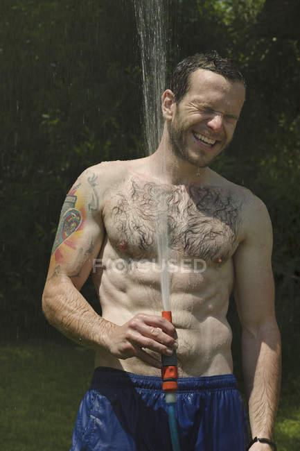 Jovem tomando banho no jardim, sorrindo — Fotografia de Stock