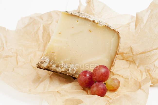 Queso Tomme de Savoie con uvas en papel pergamino - foto de stock