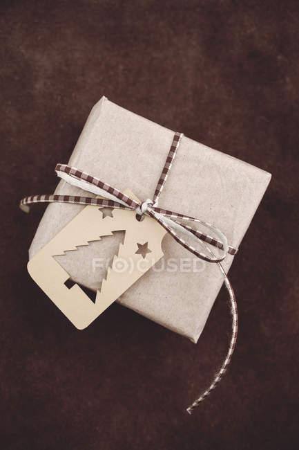 Weihnachtsgeschenk mit Geschenkanhänger auf rustikaler Lederoberfläche — Stockfoto
