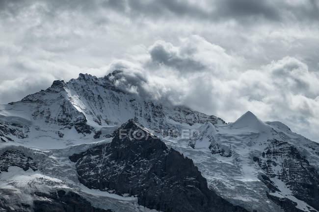 Schweiz, Berner Oberland, Jungfrau, schneebedeckten Bergkette in den Wolken — Stockfoto