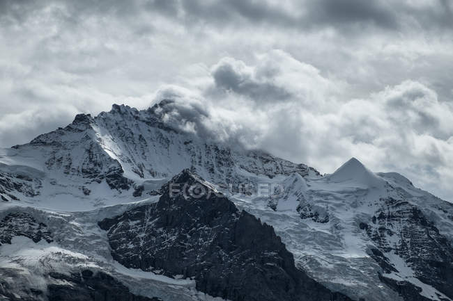Switzerland, Berner Oberland, Jungfrau, snow-covered mountain range in clouds — Stock Photo