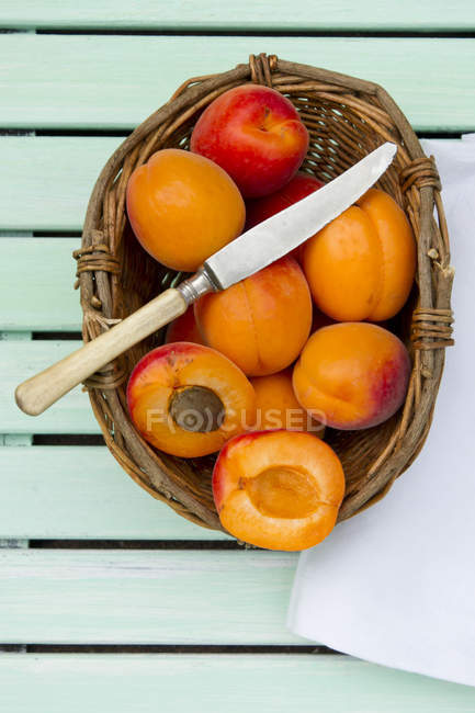 Whole and halved Apricots in basket with knife on wooden table with napkin — Stock Photo