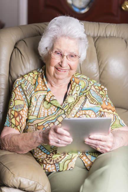 Улыбаясь возрасте женщина, глядя на планшетном компьютере — стоковое фото