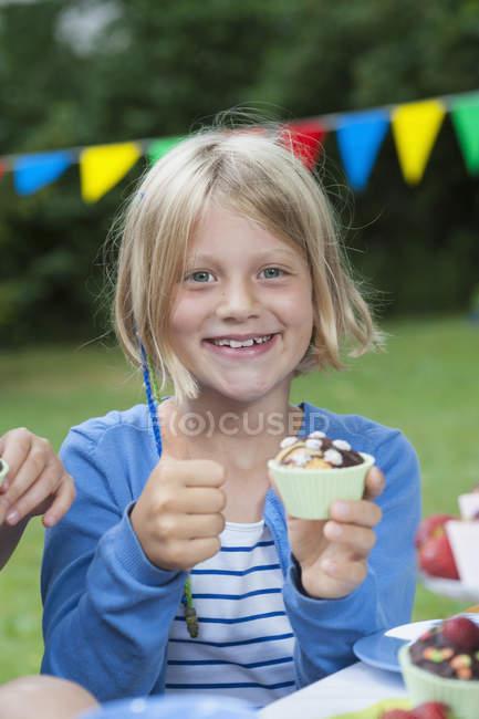 Fille heureuse manger les muffins sur une fête d'anniversaire — Photo de stock