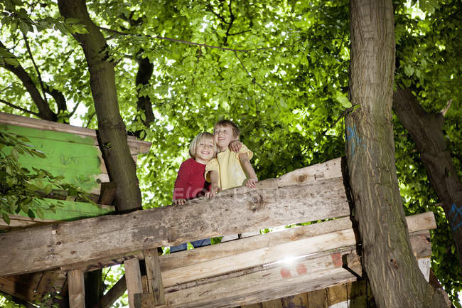 Boys playing in playground at wooden tree house, looking down — Stock Photo