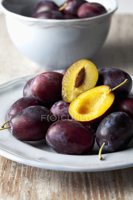Plate of whole and halved plums on wooden surface — Stock Photo