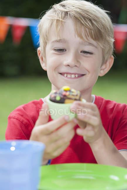 Garçon heureux de manger les muffins sur une fête d'anniversaire — Photo de stock