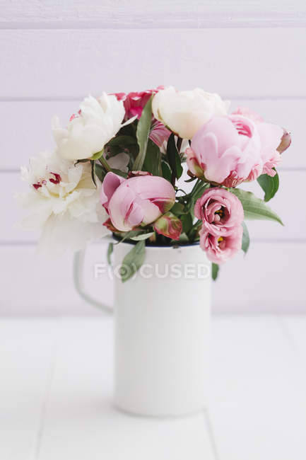 Closeup of white vase with bouquet of summer flowers on table — Stock Photo