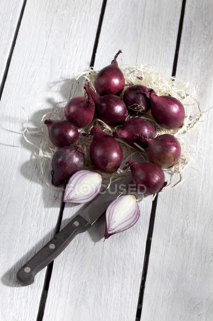Whole and halved Red pearl onions on grey wooden table with knife — Stock Photo
