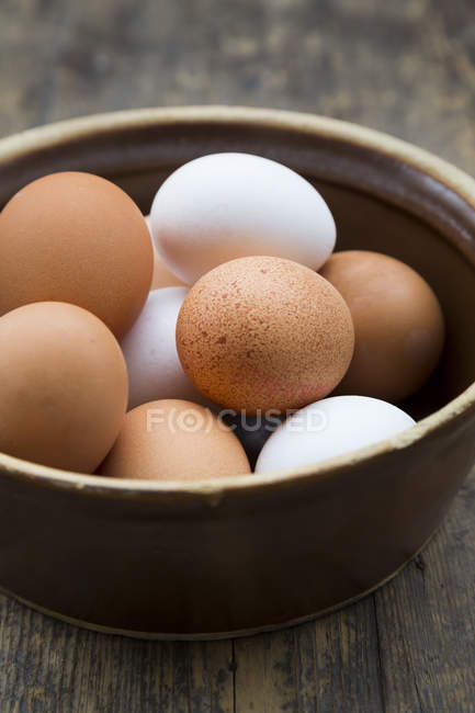 Close-up of white and brown Eggs in bowl on wooden table — Stock Photo