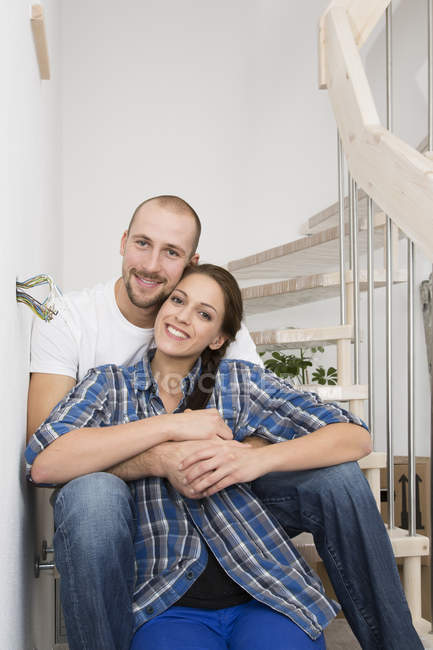 Happy young couple sitting on staircase in new home — Stock Photo