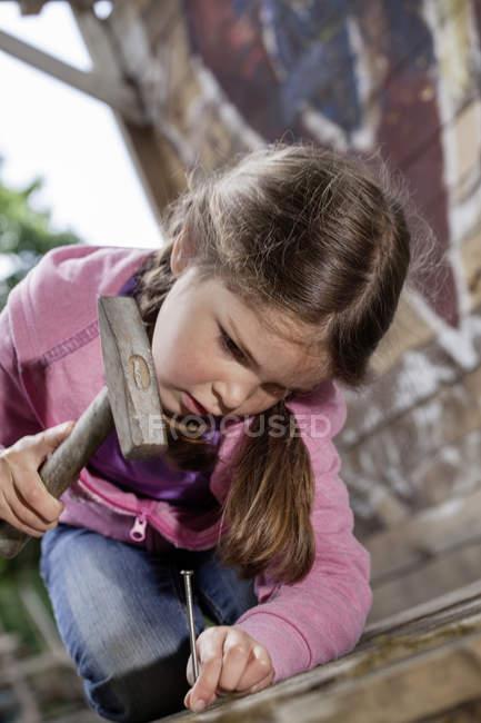 Девушка забивает гвоздь в дерево — стоковое фото