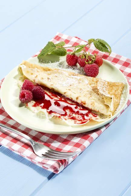 Pancakes with raspberry-jam and fresh raspberries on table — Stock Photo