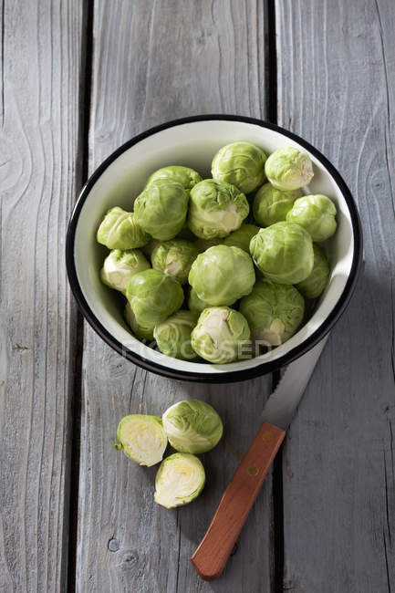 Bowl of Brussels sprouts and kitchen knife on grey wooden table — Stock Photo