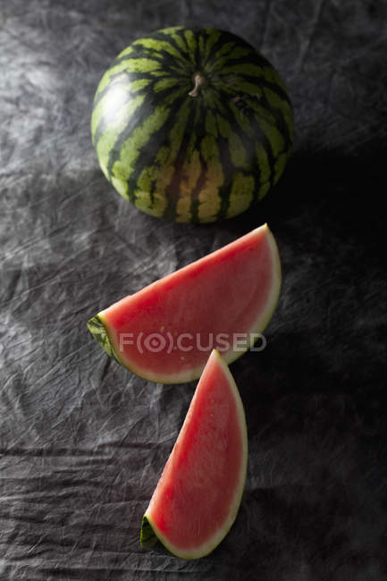 Whole watermelon with slices on black fabric — Stock Photo