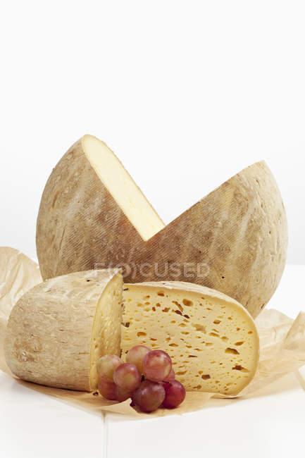Uvas en papel parafinado y queso francés Bethmale - foto de stock