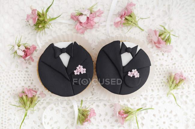 Cupcakes de novio para boda de tapete con flores - foto de stock