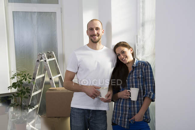 Young couple holding cups of coffee in new home — Stock Photo