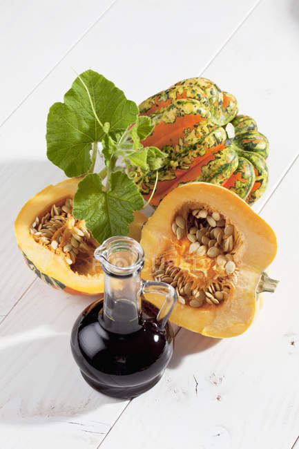 Halved and whole colorful squashes and carafe with pumpkin seed oil on white wood — Stock Photo