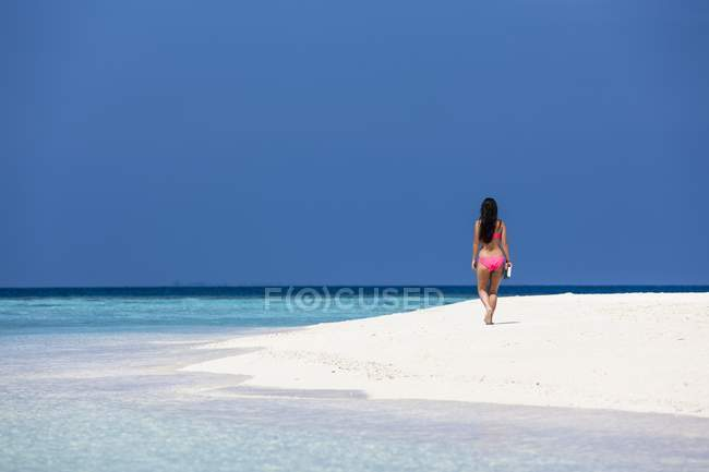 Maldive, giovane donna in bikini che cammina sulla spiaggia — Foto stock