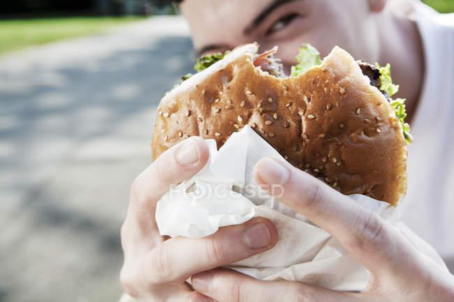Young man showing his hamburger — Stock Photo