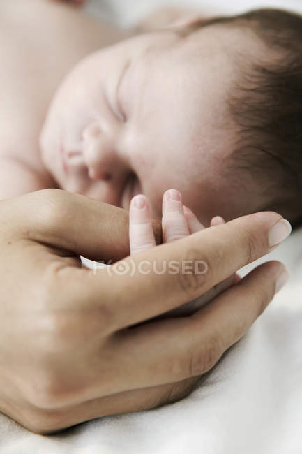 Madre che tiene per mano il figlio appena nato addormentato — Foto stock