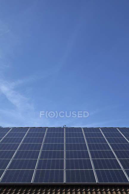 Панели солнечных батарей на крыше против неба в дневное время — стоковое фото