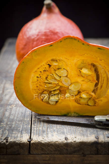Whole and halved pumpkins on wooden surface with knife — Stock Photo