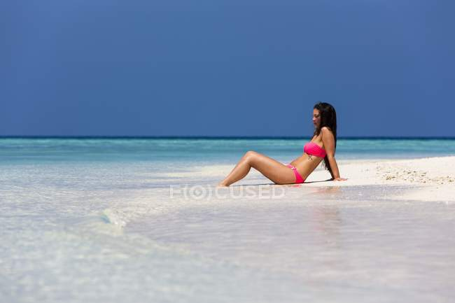Maldives, Young woman in bikini sitting in shallow water — Stock Photo