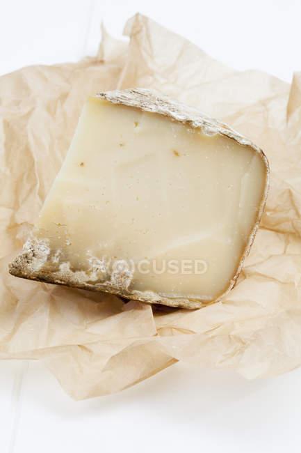 Trozo de queso de oveja francés en pergamino - foto de stock
