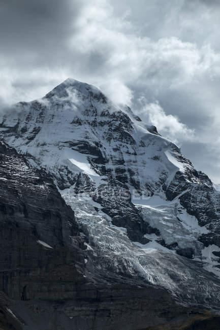 Schweiz, Berner Oberland, Moench Blick auf Gipfel mit Schnee unter Wolken — Stockfoto