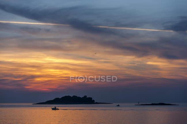Croatie, Vrsar, Coucher de soleil sur la mer avec bateau sous les nuages — Photo de stock