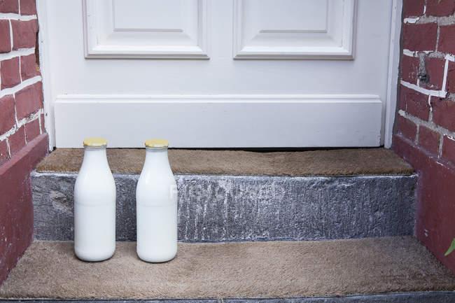 Milk bottles placed on doorstep — Stock Photo