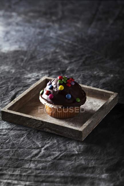 Muffin de chocolate decorado con dulces en bandeja de madera - foto de stock