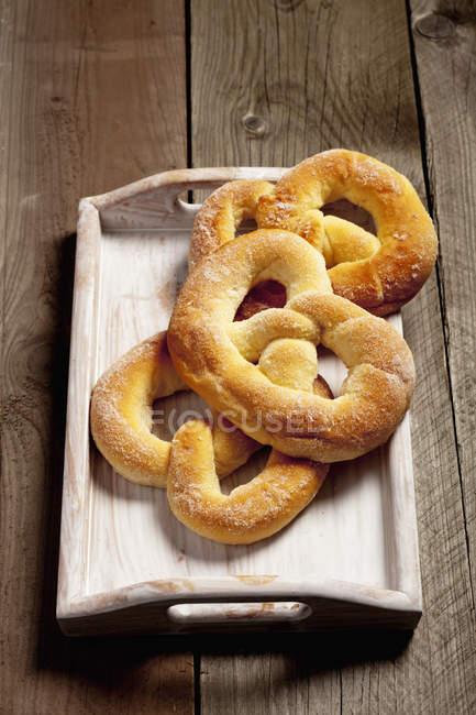 Три цукор кренделі і підношення на дерев'яні таблиці — стокове фото