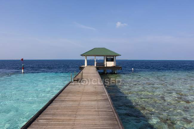 Maledives, South-Male-Atoll, Embudu, pier with barn on background over water — Stock Photo