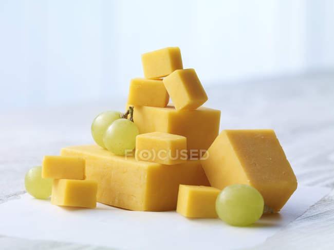 Стек кубиками Чеддер сыр с зеленым виноградом на бумаге — стоковое фото