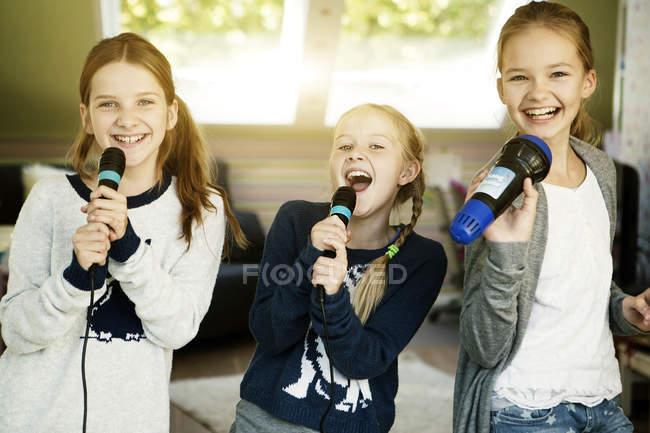 Три девочки поют с микрофонами дома — стоковое фото