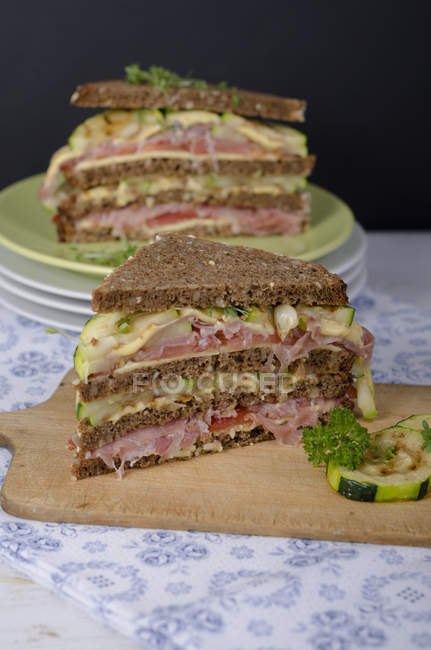 Whole-grain bread sandwiches with ham, roasted zucchini, tomatoes and cheese — Stock Photo