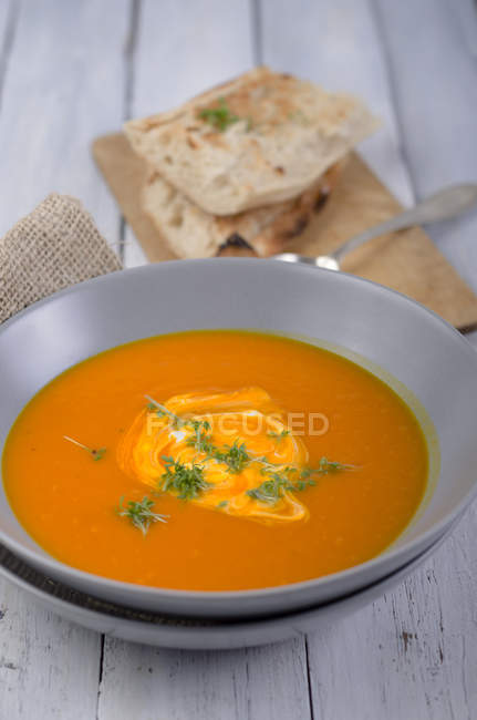 Pumpkin soup in bowl with roasted white bread on white wooden surface — Stock Photo